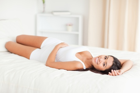 woman lying on bed in bedroom photo