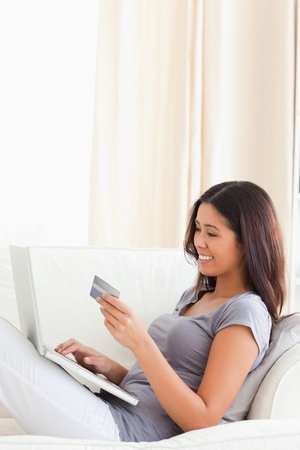 goodlooking woman sitting in livingroom on sofa holding a card photo