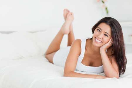 bedding indoors: happy woman lying on bed with crossed legs looking into camera in bedroom Stock Photo