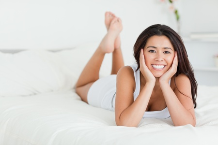 goodlooking woman lying on bed with crossed legs looking into camera in bedroom Stock Photo - 11201918