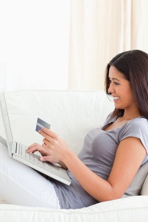 smiling woman working with notebook holding card in her hands being in livingroom photo