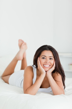 charming woman lying on bed with crossed legs looking into camera in bedroom photo