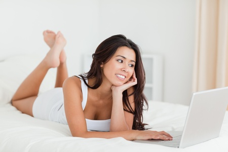 charming woman lying on bed in bedroom with crossed legs and laptop photo