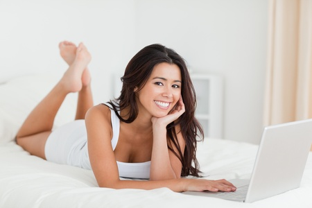 charming woman lying on bed with crossed legs and laptop looking into camera in bedroom photo