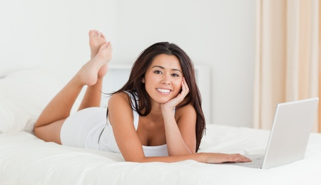 cute woman lying on bed with crossed legs and laptop looking into camera in bedroom photo