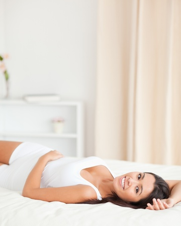 smiling woman lying on bed in bedroom Stock Photo - 11198182