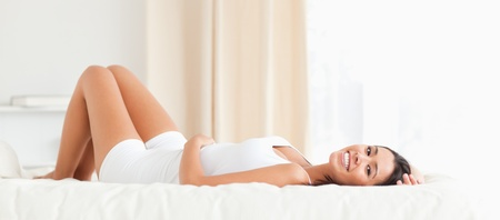 woman lying down: dark-haired woman lying on bed in bedroom Stock Photo