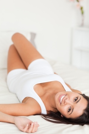 good looking woman lying on bed in bedroom photo