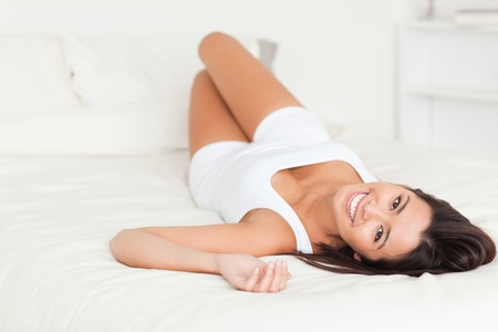 brunette woman lying on bed in bedroom photo