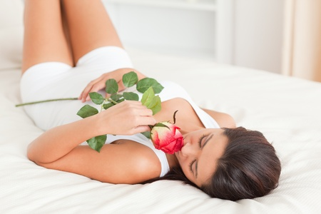 cute woman with rose lying on bed in bedroom photo