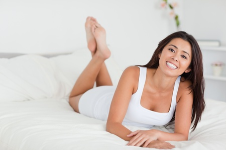 smiling woman lying on bed in bedroom with crossed legs photo