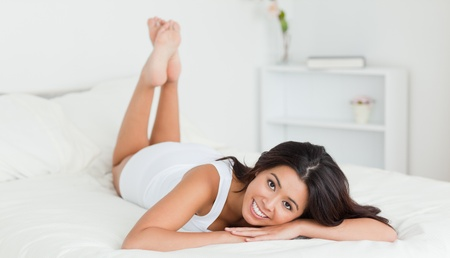 cute woman lying on bed in bedroom with crossed legs Stock Photo - 11199852