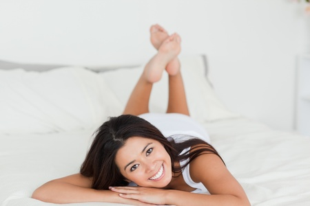 brunette woman lying on bed in bedroom with crossed legs photo