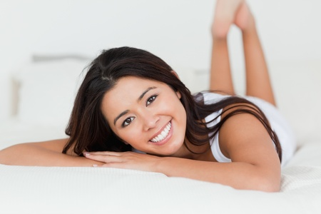 close up of a brunette woman lying on bed in bedroom with crossed legs  photo