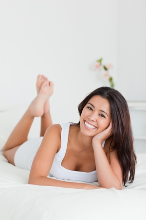 happy woman lying on bed in bedroom with crossed legs Stock Photo - 11203669