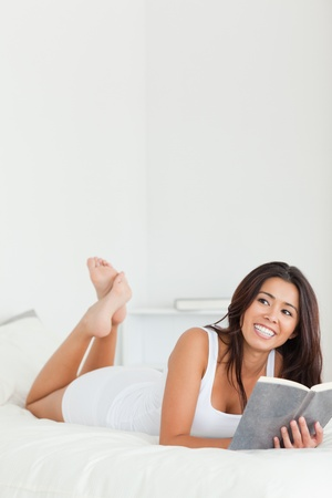 beautiful woman lying on bed with book in bedroom photo