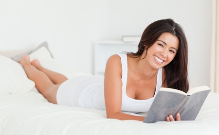 dark-haired woman lying on bed with book in bedroom photo