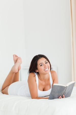 dark-haired woman lying on bed with book looking into camera in bedroom photo