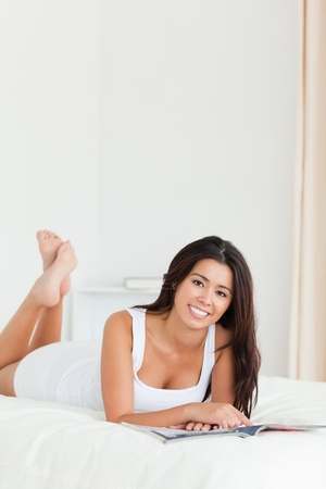 cute woman lying on bed holding a book looking into camera in bedroom photo