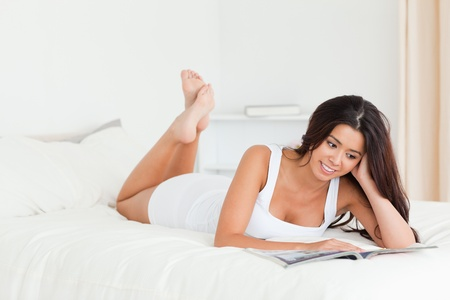 charming woman lying on bed reading a magazine in bedroom photo