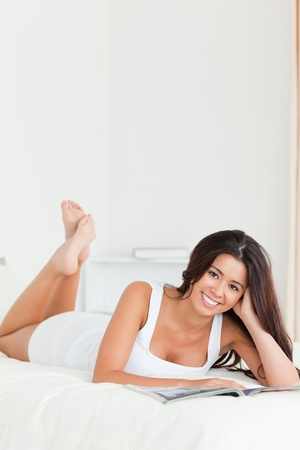 charming woman lying on bed reading a magazine looking into camera in bedroom photo