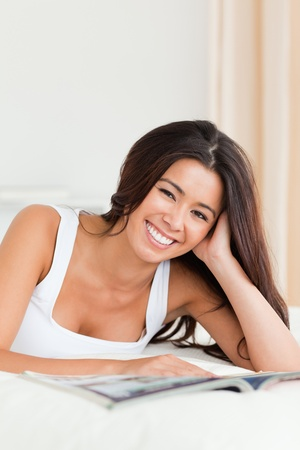 close up of a smiling woman lying on bed reading a magazine looking into camera in bedroom photo