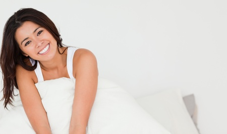 smiling woman sitting in bed in bedroom photo