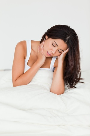 despairing beautiful woman sitting in bed in bedroom photo