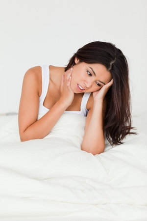 despairing goodlooking woman sitting in bed in bedroom photo