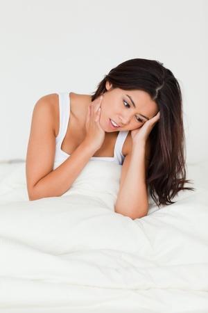 despairing goodlooking woman sitting in bed in bedroom photo