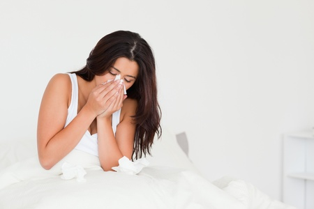 sick in bed: goodlooking woman having a cold sitting in bed in bedroom Stock Photo