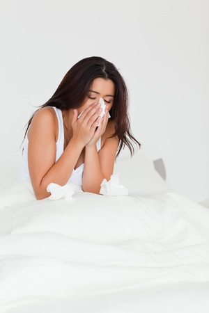 brunette woman having a cold sitting in bed in bedroom photo