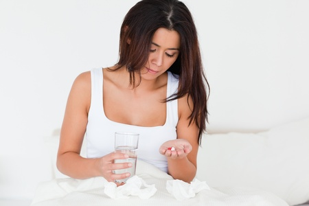 afflict: brunette woman having a cold sitting in bed taking pills in bedroom Stock Photo