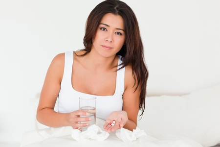 brunette woman having a cold sitting in bed taking pills looking into camera in bedroom photo