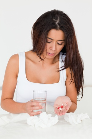 afflict: dark-haired woman having a cold sitting in bed taking pills in bedroom