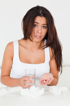 afflict: dark-haired woman having a cold sitting in bed taking pills looking into camera in bedroom Stock Photo