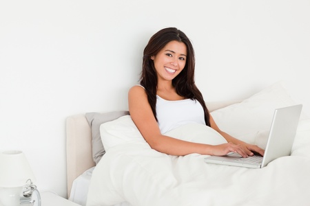 charming woman with notebook lying in bed looking into camera in bedroom photo