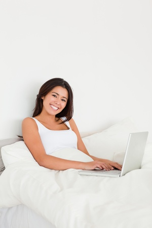 smiling woman with notebook lying in bed looking into camera in bedroom photo