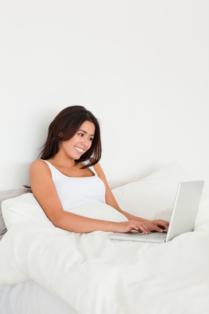 smiling woman with notebook lying in bed in bedroom photo