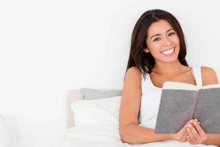 brunette woman holding book lying in bed looking into camera in bedroom photo