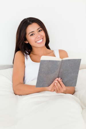 brunette woman holding book lyling in bed smiling into camera in bedroom photo