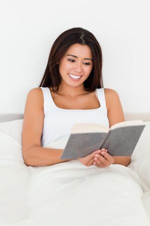 brunette woman reading book lyling in bed in bedroom photo