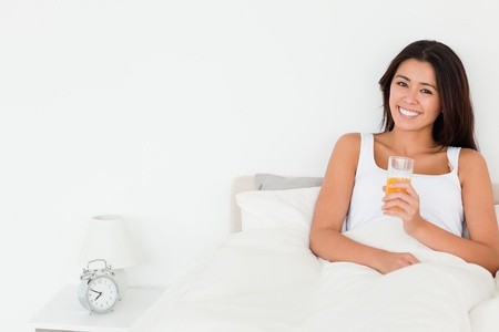 dark-haired woman dinking orange juice sitting in bed looking into camera in bedroom photo