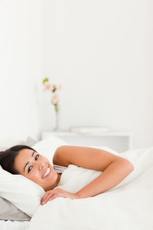 awaking: relaxing brunette woman lying under sheet in bedroom