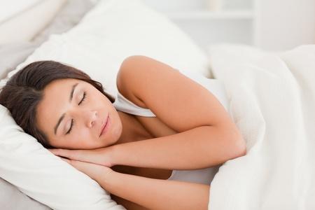 sleeping dark-haired woman lying under sheet in bedroom photo