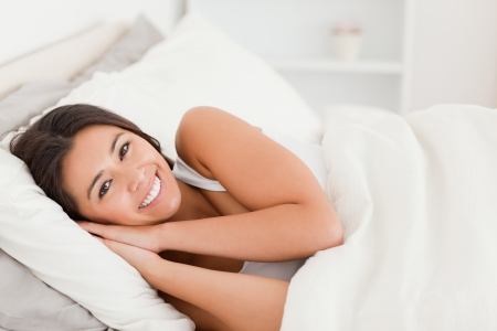 up wake: close up of a smiling dark-haired woman lying under sheet in bedroom