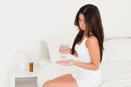 brunette woman having stomach ache taking pills in bedroom photo