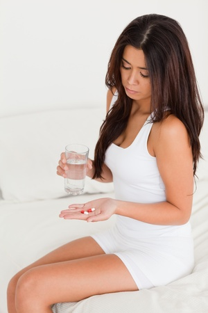 dark-haired woman having stomach ache taking pills in bedroom photo