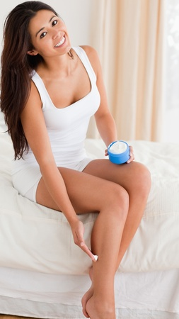 smiling woman looking into camera while putting creme on her legs in bedroom photo