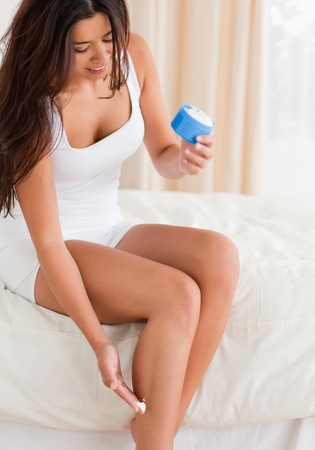 smiling woman putting creme on her legs in bedroom photo